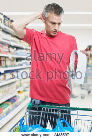 Man looking at bill in grocery store - Stock Photo