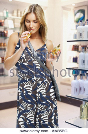 Woman testing perfumes in a store - Stock Photo