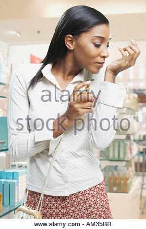 Woman testing perfume in a store - Stock Photo