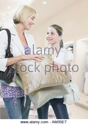 Woman and girl looking at pillows in store - Stock Photo