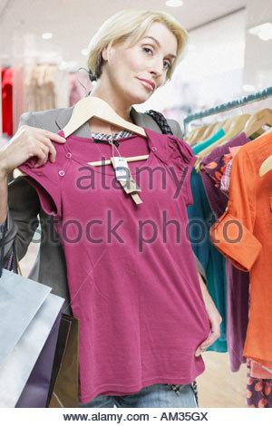 Woman holding shirt up to herself in store - Stock Photo