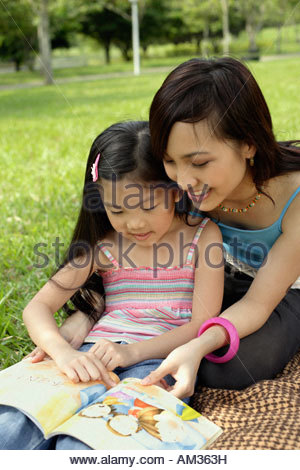 Woman and young girl reading in park - Stock Photo