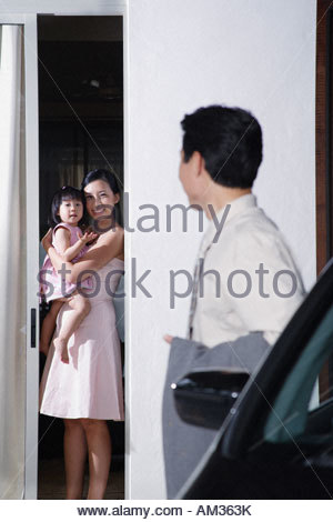 Woman and young girl with man standing by car - Stock Photo