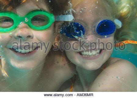 Young boy and girl wearing swim goggles underwater - Stock Photo