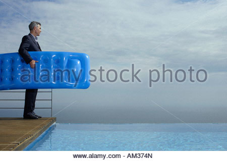 Man standing on deck by infinity pool - Stock Photo