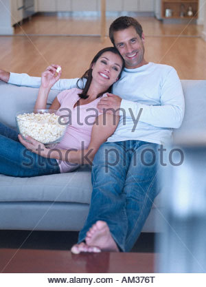 Woman and man on sofa with popcorn watching television - Stock Photo