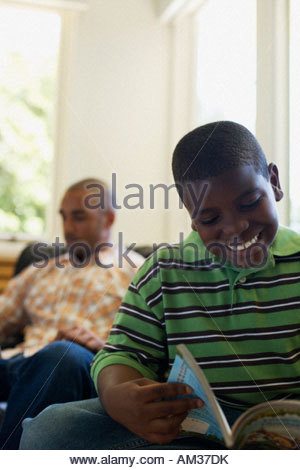 Young boy reading book with man in background - Stock Photo