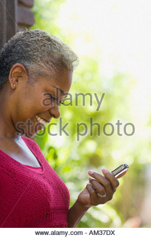 Woman looking at her mobile phone outdoors - Stock Photo