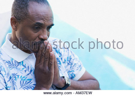 Man with hands to lips thoughtfully by pool - Stock Photo