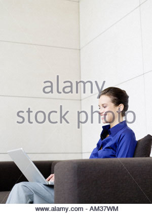 Businesswoman sitting on sofa using laptop smiling - Stock Photo