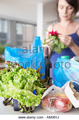 Woman with groceries and flowers in kitchen - Stock Photo