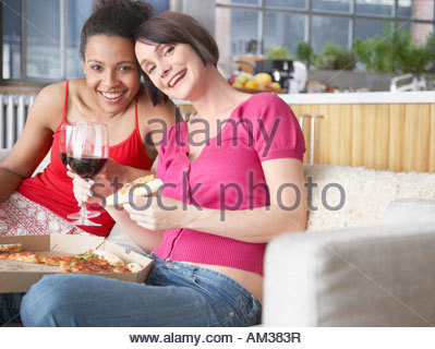 Two women on sofa with wine and pizza - Stock Photo