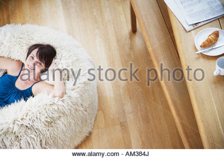 Woman on furry bean bag chair in living room - Stock Photo
