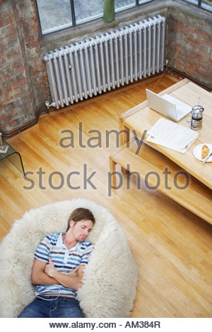 Man wearing earbuds on furry bean bag chair - Stock Photo
