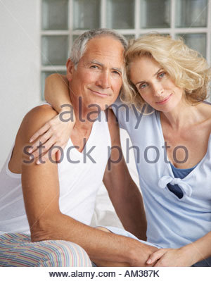 Couple in bed relaxing - Stock Photo