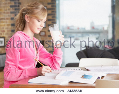 Girl writing in notebook holding glass of milk - Stock Photo