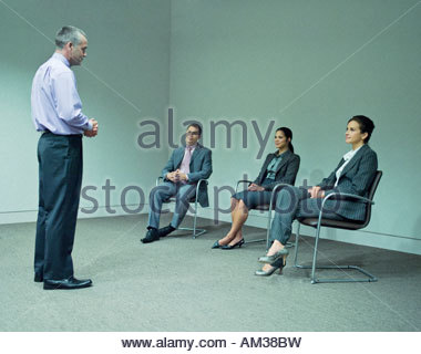 Man giving presentation to three co-workers - Stock Photo