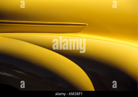 Detail of the front end of a British antique yellow car showing the flowing curves of the front fender and hood - Stock Photo