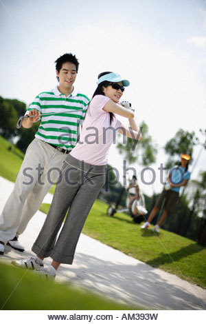 Couple golfing with woman in background - Stock Photo