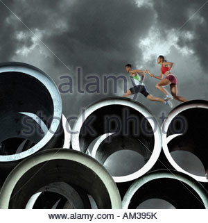 Two relay runners going across large cylinders - Stock Photo