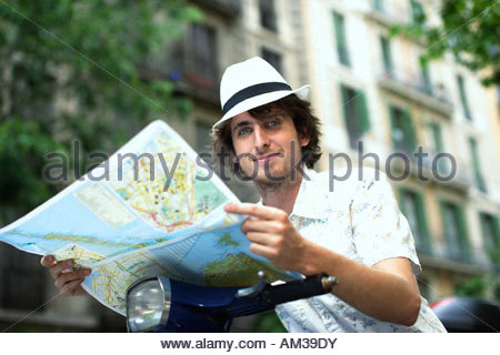Man on scooter with map outdoors - Stock Photo