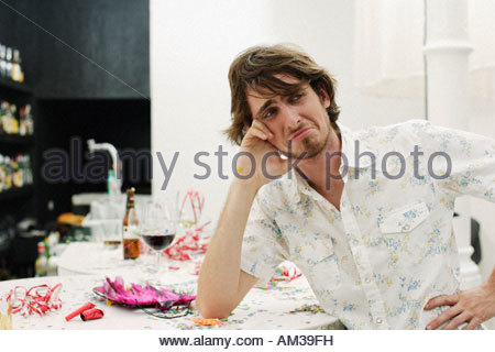 Man looking sad leaning on table - Stock Photo