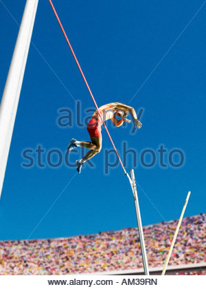 Athlete in mid air doing pole vault - Stock Photo