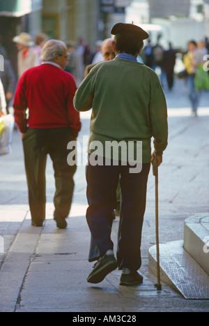 Elderly men walking along a busy street in Segovia Castilla y Leon Spain One man walks with a cane and wears a beret - Stock Photo