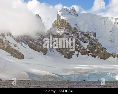 Clouds above the snow covered mountains near the entrance to Paradise Harbor aka Paradise Bay Antarctica - Stock Photo