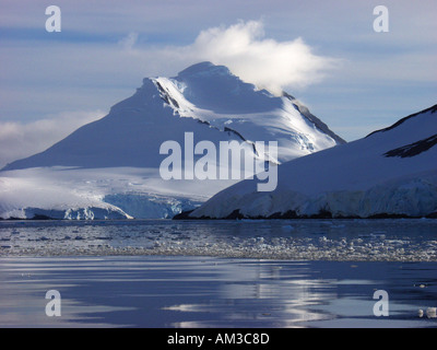 Clouds atop a snow covered mountain in Paradise Harbor aka Paradise Bay Antarctica - Stock Photo