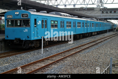 An efficient and on time Japan Railways local train arriving at a station in Osaka Kansai Japan - Stock Photo