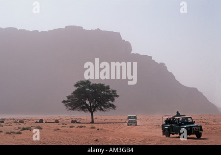 Floor of the desert with outcrops called Jebels in the distance Jeeps crossing the desert floor Wadi Rum Jordan - Stock Photo