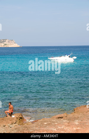 Power boat anchored in the turquoise bay, Platges de Comte, Ibiza - Stock Photo