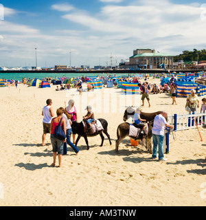 Children on donkeys at British seaside beach in summer at Weymouth beach in Dorset, England, UK - Stock Photo