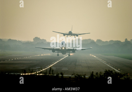 One jet takes off as another comes in to land at London Gatwick airport at dawn - Stock Photo