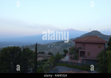 Mt Etna emitting steam and smoke as seen from Taormina at sun rise Sicily Italy July 2006 - Stock Photo
