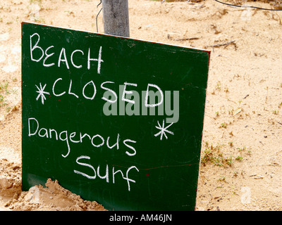 A sign indicating that a surf beach is closed due to dangerous conditions. - Stock Photo