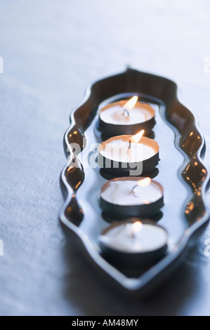 Close-up of four aromatherapy candles burning in a tray - Stock Photo