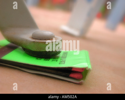 matchbook under table leg as a solution to a wobbly or shaky table - Stock Photo