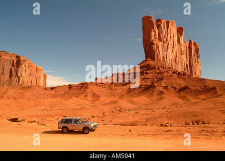 A four wheel drive SUV on a dirt road through Monument Valley, Arizona. - Stock Photo