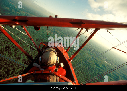 red open cockpit bi plane in a steep turn - Stock Photo