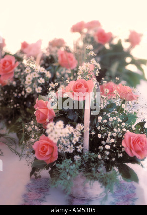 wedding flower basket of pink roses and Baby's Breath on a reception table - Stock Photo