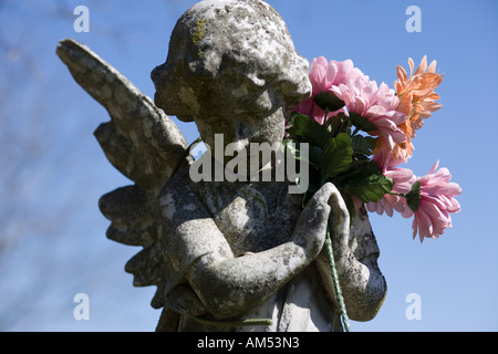 Stone angel with plastic flowers in a US graveyard. Shallow focus. - Stock Photo