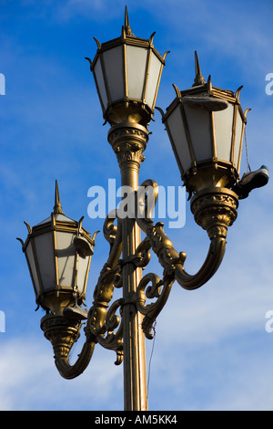Old soccer football shoes trainers sneakers dangling from an ornate vintage streetlamp in Buenos Aires - Stock Photo