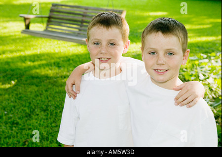 Closeup of twin boys with arms around each other, portrait. - Stock Photo
