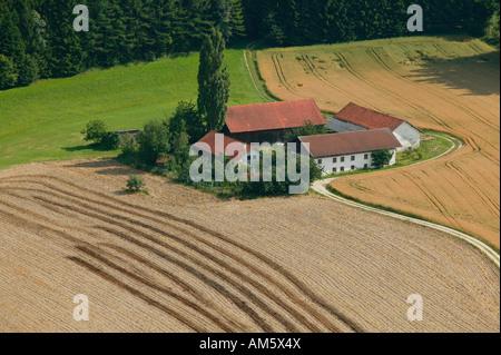 Farm between harvested grainfields, Lower Bavaria, Bavaria, Germany - Stock Photo