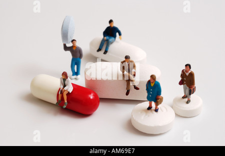 Group of tiny figures standing on sitting on and holding a variety of pills and capsules - Stock Photo
