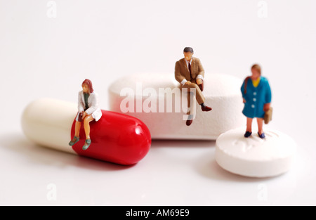 Three tiny figures standing and sitting on pills - Stock Photo
