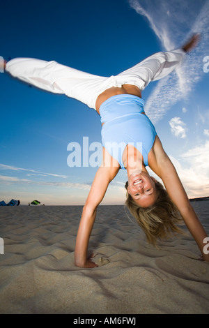 Young woman doing a handstand on the beach - Stock Photo