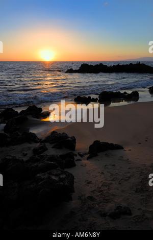 Beatiful sunset at the rock and sand beach in Wailea Maui Hawaii USA - Stock Photo